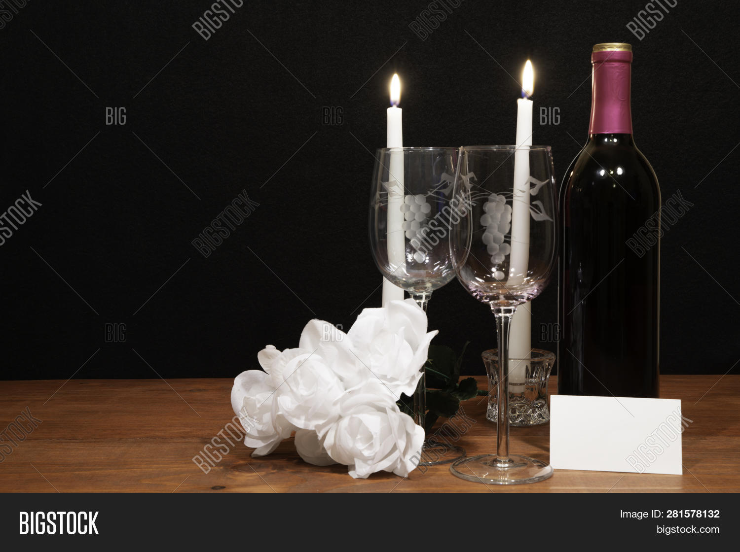 907e715c030a Beautiful etched wine glasses and bottle of red wine, white candles and  bouquet of white roses on wooden table with card on dark background.