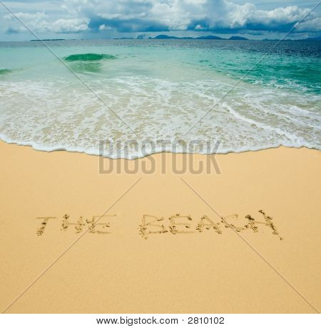 the beach written in a sandy tropical beach poster
