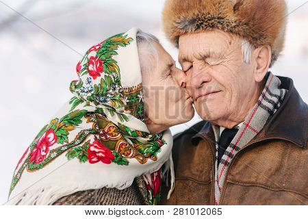 Portrait Of Happy Senior Couple. Elderly Woman Kiss Her Husband In Weighty. Old Couple Walkink In Th