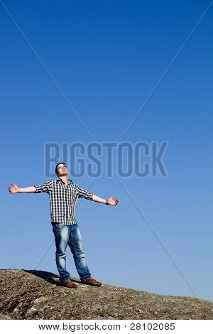 young casual man with the sky as background