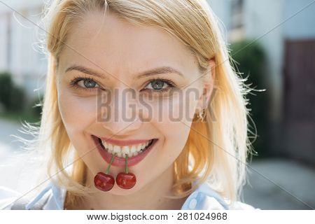 A Reason To Smile. Happy Woman Hold Cherry Berries In Healthy Teeth. Sensual Woman With White Smile.
