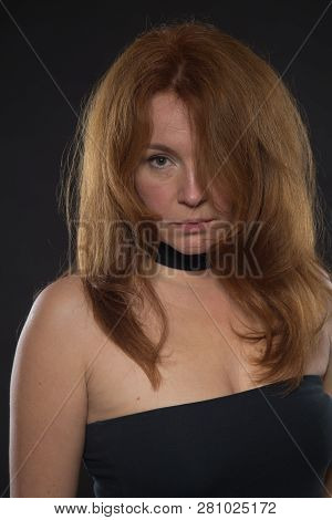 Tranquil glance of self controlled bare shouldered woman in black dress standing in front of you while looking straight at camera poster