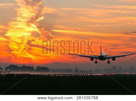 Takeoff Of A Passenger Plane On The Background Of A Sunset. Flight Of The Air Liner At Sunset.