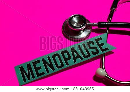 Menopause on the paper with healthcare concept. With stethoscope on pink bakcground poster