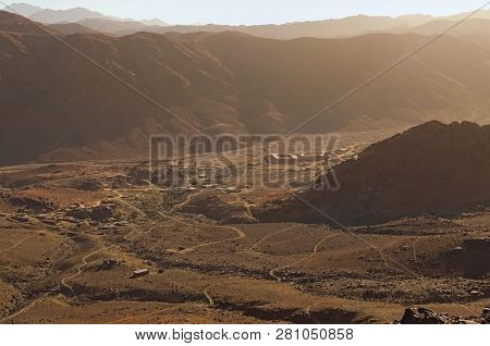 poster of Aerial view of small village in the valley between high mountains. View from Mount Sinai (Mount Horeb, Gabal Musa). Sinai Peninsula of Egypt. Winter landscape photo.