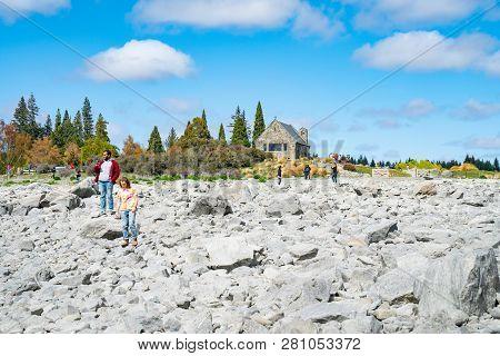 Lake Tekapo New Zealand - October 14 2018; Tourists  Clambering Over Rocks Enjoy Experience Of Rocky