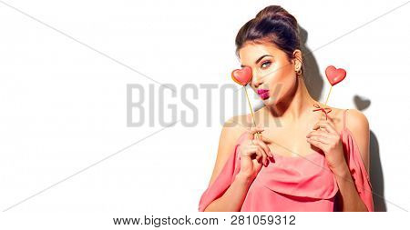 Beauty joyful Young fashion model Girl with Valentine Heart shaped cookies in her hands. Love Concept. Beautiful smiling young woman. Kiss. Valentines Day gift. Isolated on white background