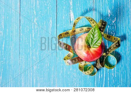Healthy Food Concept. Apple And Tape Measure On Wooden Background