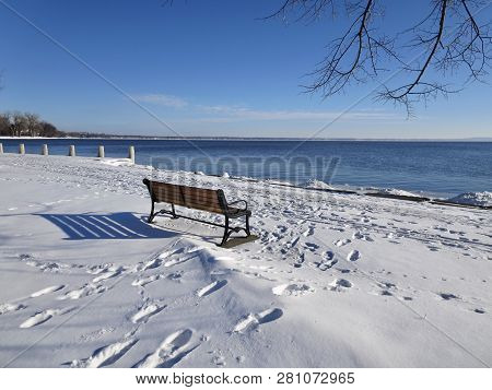 Footprints In The Snow Suggest That Early Spring Visitors Have Been By To See The Open Water On The