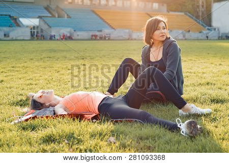 Healthy Lifestyle, Healthy Family. Smiling Fitness Mother And Teen Daughter Together Resting At Stad