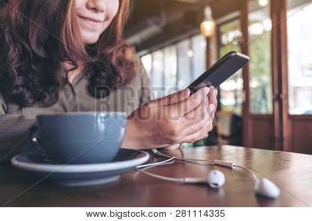 Closeup Image Of A Woman Using Mobile Phone While Listening To Music With Earphones And Coffee Cup O