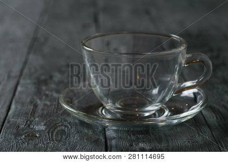 Empty Glass Cup With Saucer On Wooden Rustic Wooden Table.