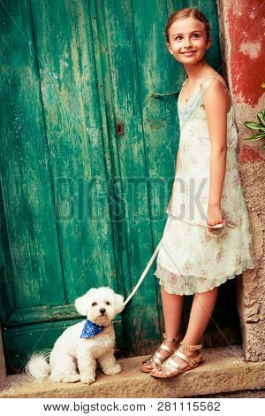 Portrait of a cute girl with white Maltese dog on a old doors background.