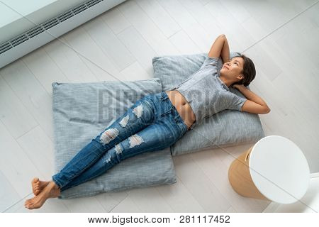 Home lifestyle happy Asian woman relax lying down on living room floor pillows relaxing contemplative looking at windows. New condo apartment satisfaction homeowner young girl enjoying house.