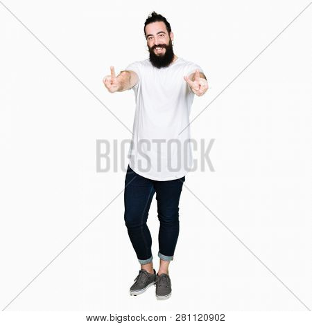 Young hipster man with long hair and beard wearing casual white t-shirt smiling looking to the camera showing fingers doing victory sign. Number two.