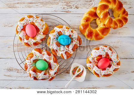 Homemade Sweet Italian Easter Bread Rings With Dyed Eggs On A N Old White Wooden Table, View From Ab