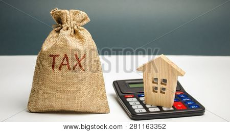 A Bag With The Word Tax And Calculator With A House. Taxes On Real Estate, Payment. Penalty, Arrears