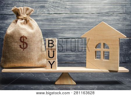 A Money Bag And Wooden Blocks With The Word Buy And A Miniature House On Scales. The Accumulation Of