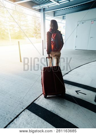 Woman Exiting Airport Parking Carrying Big Red Luggage Walking To The Terminal To Catch Her Flight