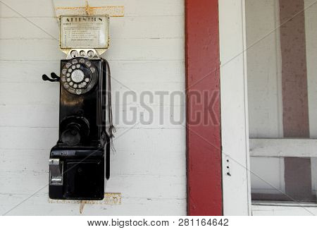 Antique Payphone. Old Obsolete Rotary Payphone Mounted To The Wall.