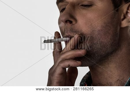 Close up on nicotine addicted man smoking cigarette. Unhealthy habbit may couse lung cancer.