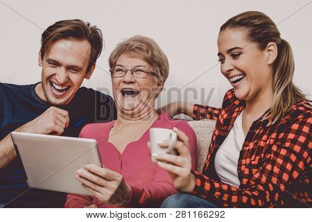 Happy adult kids with elderly mother on couch witch tablet computer. Mothers day concept.