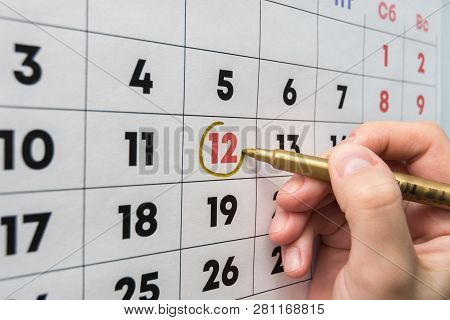 Hand With A Marker On The Wall Calendar Leads Around A Red Holiday