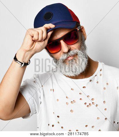 Old Brutal Senior Rich Man In Designer T-shirt Holds The Visor Of His Blue And Red Baseball Cap Styl
