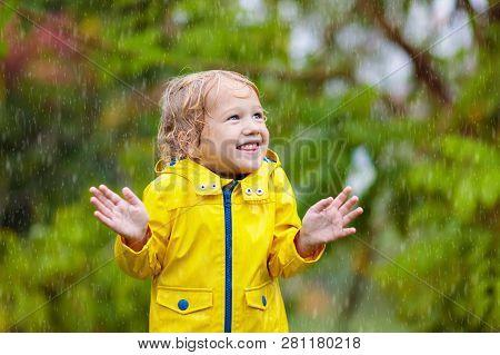 Kids Play In Autumn Rain. Child On Rainy Day.