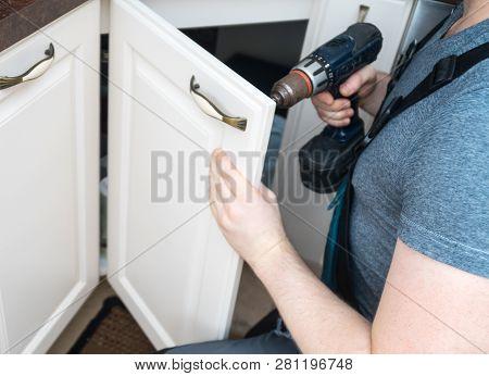 A Professional Handyman Assembling Kitchen Door Cabinet.