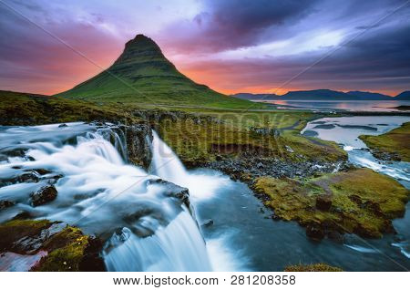 Beautiful view of unusual Kirkjufell volcano at sunset. Location place Kirkjufellsfoss waterfall, Iceland, Europe. Picturesque image of most popular tourist attraction. Explore the beauty of earth.