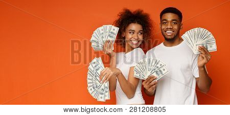 Happy Millennial Couple Posing With Lot Of Money, Holding With Dollar Fans, Orange Panorama Backgrou