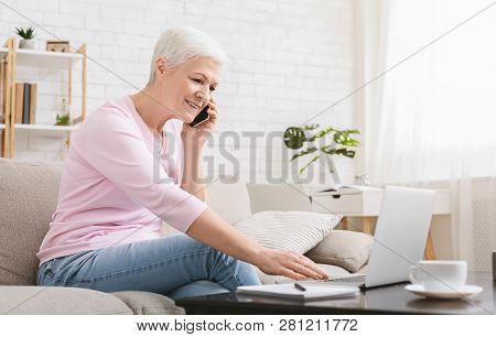 Freelance For Any Age. Ambitious Elderly Lady Managing Project From Home, Talking On Phone And Using