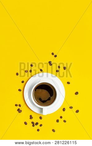 Flat Lay Cup Of Black Coffee And Coffee Beans On Yellow Background Top View Copy Space. Minimalistic