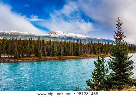 Picturesque lake with azure water among the mountains and multicolored coniferous forests. Grand Autumn in the Rockies of Canada. The concept of active, photo and eco-tourism