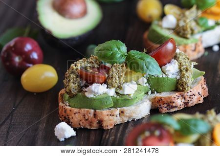 Avocado Toast Sandwich With Avocados, Pesto, Feta Cheese, Fresh From The Garden Basil And Heirloom T
