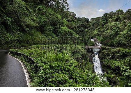 Road To Hana:  The Hana Highway Turns To Cross A One Lane Bridge Beside A Waterfall On The North Coa