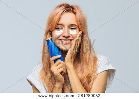 Portrait Of Young Joyful Cute Woman Smiling And Applying Suntan Cream (sunscreen Lotion) On Face. Pr