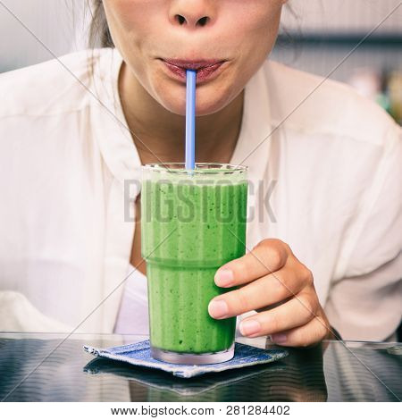 Green smoothie drink healthy detox diet woman drinking matcha tea cold juice beverage. Square crop for social media.