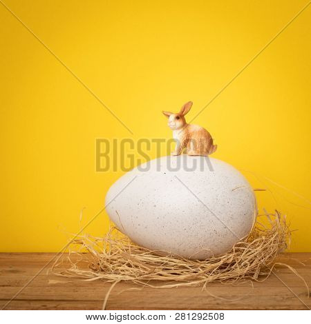 A sweet Easter Bunny is sitting on a big egg yellow background
