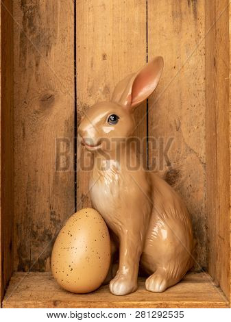 A sweet easter bunny figure with an egg in a wooden box