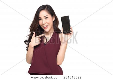 Portrait Of A Cheerful Beautiful Girl Wearing Red Dress And Showing Or Presenting Mobile Phone Appli