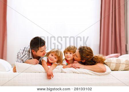 Family Portrait von Mama Papa und Zwillinge Töchter auf Bett