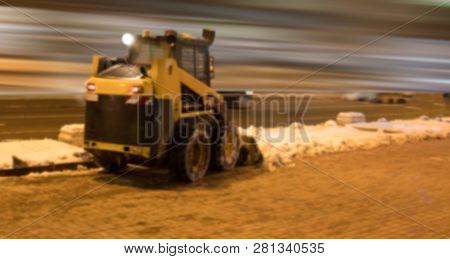 Blurred Background. Night City Lights Blur. Snow Removal Vehicle Removing Snow.