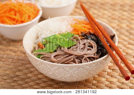 Soba noodle soup with nori seaweed sheets, green beans, carrot, and daikon radish