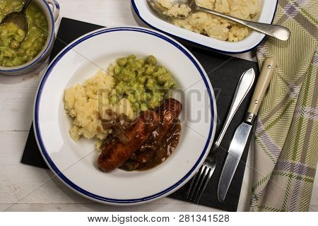 Very Typical Irish Dish, Mashed Potato, Onion Gravey, Grilled Sausages And Mushy Peas