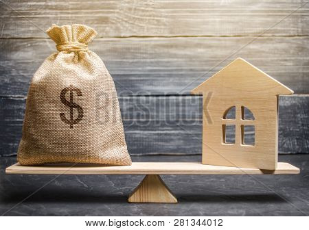 A Money Bag And A Wooden House On The Scales. The Concept Of Real Estate Purchase. Sale Of Property.