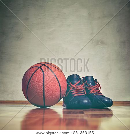 Basketball Background. A Pair Of Basketball Shoes On A Hardwood Floor Next To A Basketball. Retro To