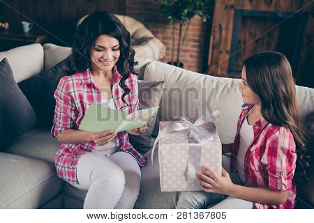 Close up photo two people mum little daughter giving present box card with mommy poem unexpected sweet cute reading delighted wear pink plaid shirts flat apartment room sit cozy couch sofa divan poster