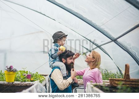 Eco And World Environment. Happy Family In Greenhuse As Ymbol Of Eco And World Environment. Eco And